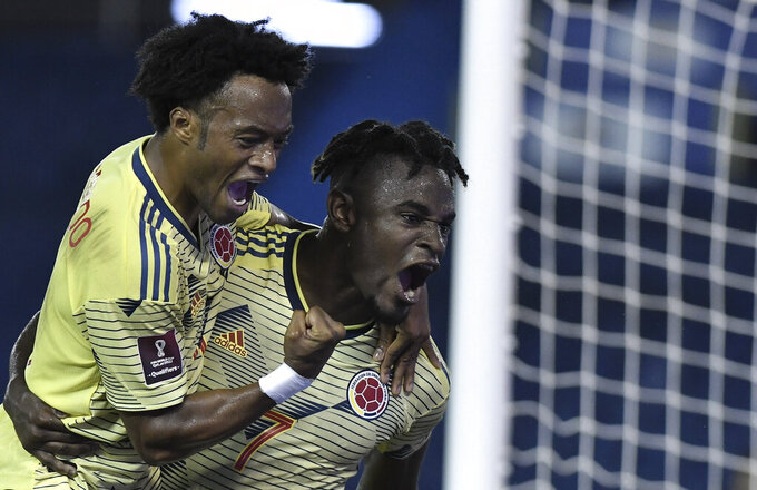 Colombia's Duvan Zapata, right, celebrates scoring his side's first goal with teammate Juan Cuadrado during a qualifying soccer match against Venezuela for the FIFA World Cup Qatar 2022 in Barranquilla, Colombia, Friday, Oct. 9, 2020. (Gabriel Aponte/Pool via AP)
