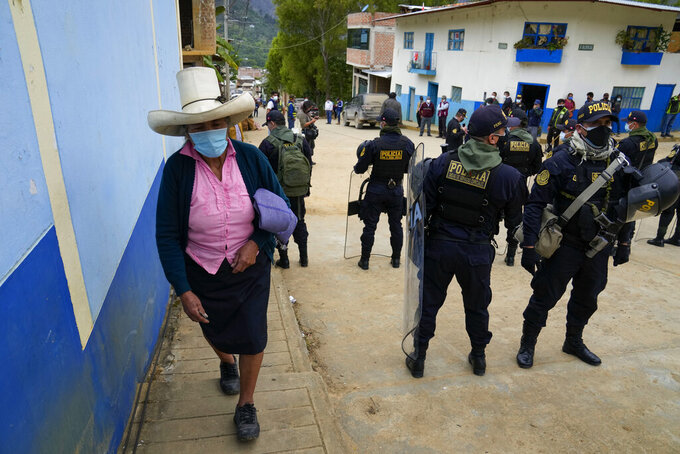 A voter arrives to a polling station guarded by police in Tacabamba, Peru, Sunday, June 6, 2021. Peruvians vote Sunday in a presidential run-off election to choose between Pedro Castillo, a political novice who until recently was a rural schoolteacher, and Keiko Fujimori, the daughter of jailed ex-President Alberto Fujimori. (AP Photo/Martin Mejia)