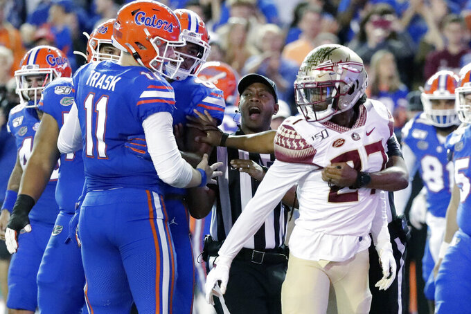 Officials break up an argument between Florida quarterback Kyle Trask (11) and Florida State defensive back Akeem Dent (27) during the first half of an NCAA college football game Saturday, Nov. 30, 2019, in Gainesville, Fla. (AP Photo/John Raoux)