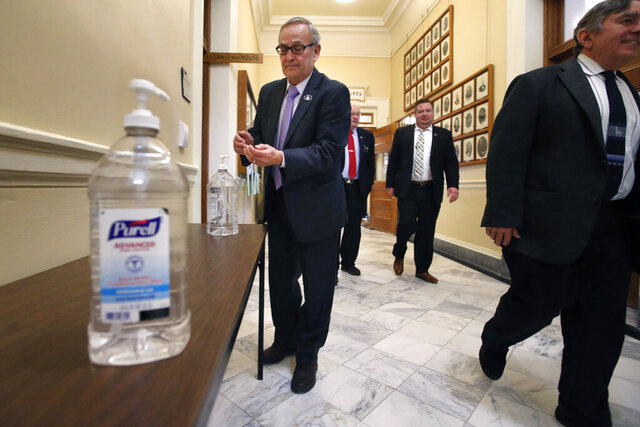 Bottles of hand sanitizer are made available for lawmakers outside the House Chamber at the State House, Tuesday, March 17, 2020, in Augusta, Maine. The Maine Legislature convened to consider coronavirus-related legislation and a budget bill. (AP Photo/Robert F. Bukaty)