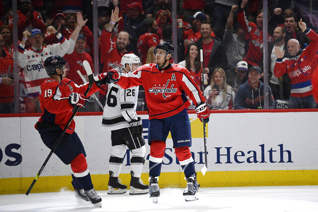 Washington Capitals defenseman John Carlson, right, celebrates his goal with center Nicklas Backstrom (19), of Sweden, during the second period of an NHL hockey game, as Los Angeles Kings defenseman Sean Walker (26) skates by, Tuesday, Feb. 4, 2020, in Washington. (AP Photo/Nick Wass)