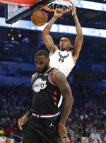 CORRECTS TO THE LAKERS, NOT THE CAVALIERS - Team Giannis' Giannis Antetokounmpo, of the Milwaukee Bucks, dunks the ball against Team LeBron's LeBron James, of the Los Angeles Lakers, during the first half of an NBA All-Star basketball game, Sunday, Feb. 17, 2019, in Charlotte, N.C. (AP Photo/Chuck Burton)