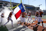 FILE - In this Nov. 7, 2020, file photo,T exas players run onto the field for an NCAA college football game against West Virginia in Austin, Texas. The Wild West nature of the upcoming college football season can be illustrated in part by 160 miles of Texas highway that connects the trendy college city of Austin with the bustling metropolis of Houston. (AP Photo/Chuck Burton, File)