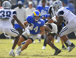 Los Angeles Rams running back Jake Funk runs between Dallas Cowboys' Israel Mukuamu, left, and Austin Faoliu during NFL football practice Saturday, Aug 7, 2021, in Oxnard, Calif. (AP Photo/John McCoy)