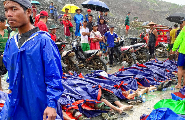 People gather near the bodies of victims of a landslide near a jade mining area in Hpakant, Kachin state, northern Myanmar Thursday, July 2, 2020. Myanmar government says a landslide at a jade mine has killed dozens of people.  (AP Photo/Zaw Moe Htet)