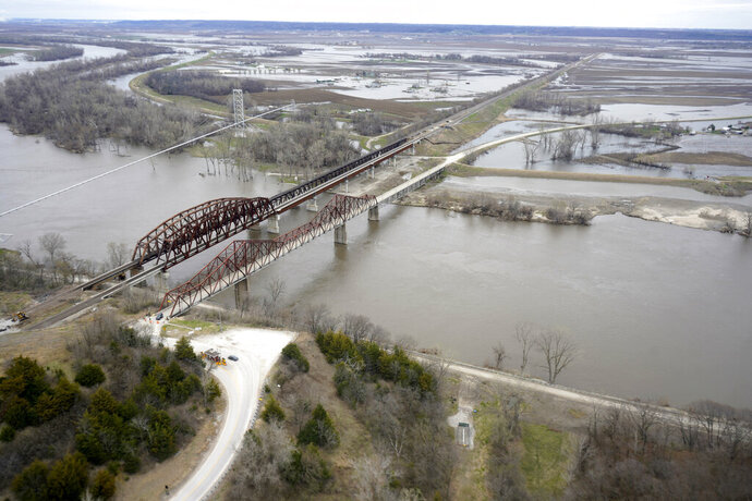 In this Friday, April 12, 2019 photo, bridges over the Missouri River connect Plattsmouth, Neb., bottom, and Mills County, Iowa, top. This spring's massive flooding along the Missouri River unearthed bitter criticism of the federal agency that manages the river while devastating communities and causing more than $3 billion in damage. The flooding and the U.S. Army Corps of Engineers' actions will be the focus of a U.S. Senate hearing in western Iowa on Wednesday, April 17, and critics will demand the agency make flood control its top priority. (AP Photo/Nati Harnik)