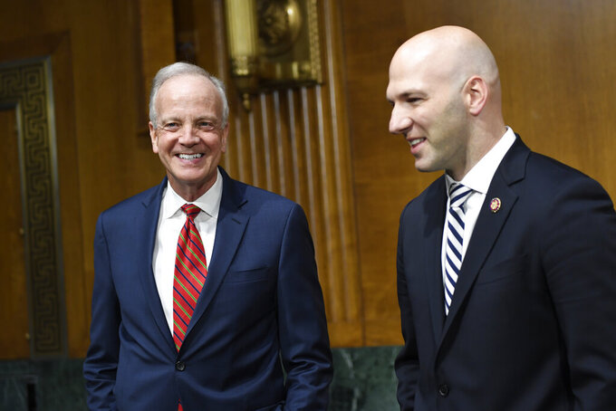 Senate Commerce subcommittee chairman Sen. Jerry Moran, R-Kan., left, talks with Rep. Anthony Gonzalez, R-Ohio, right, before the start of a hearing on Capitol Hill in Washington, Tuesday, Feb. 11, 2020, on intercollegiate athlete compensation. (AP Photo/Susan Walsh)