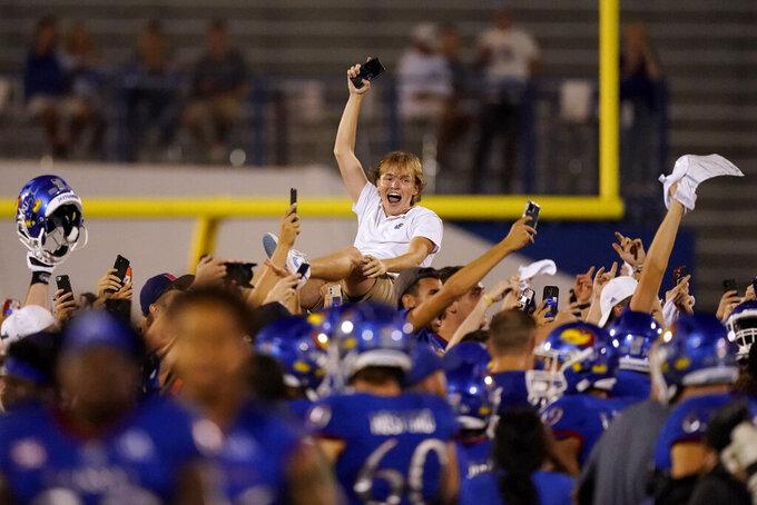 A fan celebrates on the field after an NCAA college football game between Kansas and South Dakota Friday, Sept. 3, 2021, in Lawrence, Kan. Kansas won 17-14. (AP Photo/Charlie Riedel)
