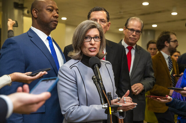 Sen. Joni Ernst, R-Iowa, with, from back left, Sen. Tim Scott, R-S.C., Sen. John Barrasso, R-Wyo., and Sen. Mike Braun, R-In., speaks to reporters on Capitol Hill in Washington, Saturday, Jan. 25, 2020. (AP Photo/Manuel Balce Ceneta)