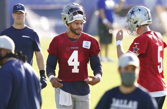 Dallas Cowboys quarterback Dak Prescott (4) talks with teammate Clayton Thorson (5) during an NFL football training camp practice in Frisco, Texas, Friday, Aug. 14, 2020. (AP Photo/LM Otero)