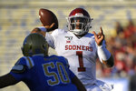 Oklahoma quarterback Jalen Hurts, right, throws a pass as UCLA defensive lineman Tyler Manoa defends during the first half of an NCAA college football game Saturday, Sept. 14, 2019, in Pasadena, Calif. (AP Photo/Mark J. Terrill)