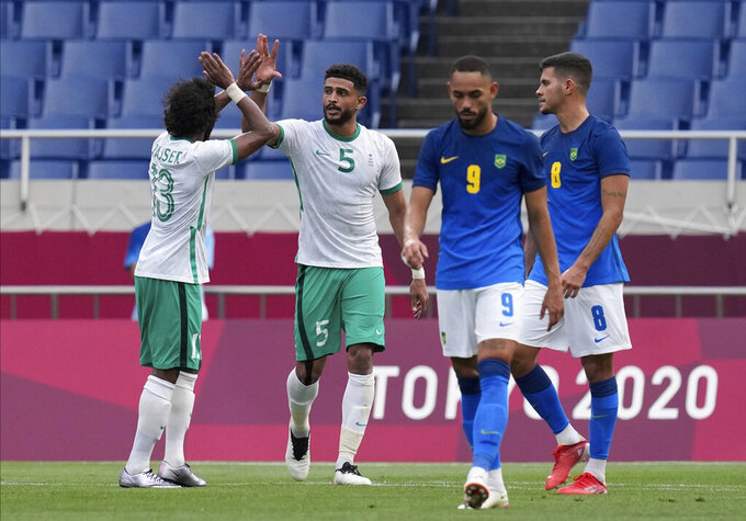 Saudi Arabia's Abdulelah Alamri, second left, celebrates with his teammate Yasser Alshahrani after scored his side's first goal against Brazil during a men's soccer match at the 2020 Summer Olympics, Wednesday, July 28, 2021, in Saitama, Japan. (AP Photo/Martin Mejia)