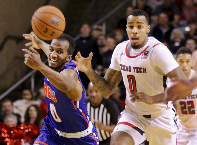 After recovering a rebound, Texas Tech's Kyler Edwards (0) has the ball knocked out of his hands from behind by Houston Baptist's Ian Dubose (0) during the first half of an NCAA college basketball game Wednesday, Nov. 13, 2019, in Midland, Texas. (Ben Powell/Odessa American via AP)
