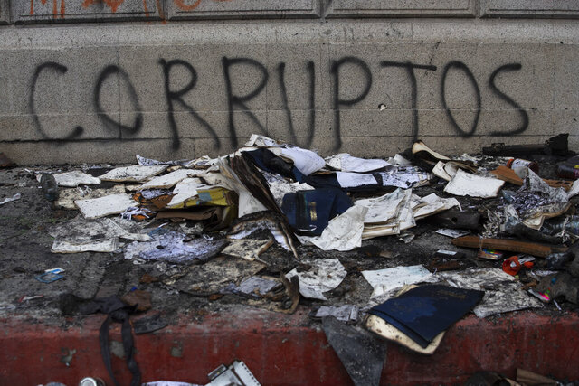 Debris lays in front of graffiti that reads in Spanish