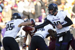 Northwestern quarterback Clayton Thorson hands the ball off to running back Isaiah Bowser during an NCAA college football game against Minnesota, Saturday, Nov. 17, 2018, in Minneapolis. Northwestern won 24-14. (AP Photo/Stacy Bengs)