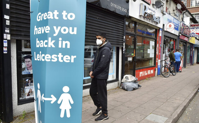 People walk past closed shops in Leicester, England, Tuesday June 30, 2020. The British government has reimposed lockdown restrictions in the English city of Leicester after a spike in coronavirus infections, including the closure of shops that don't sell essential goods and schools. (AP Photo/Rui Vieira)