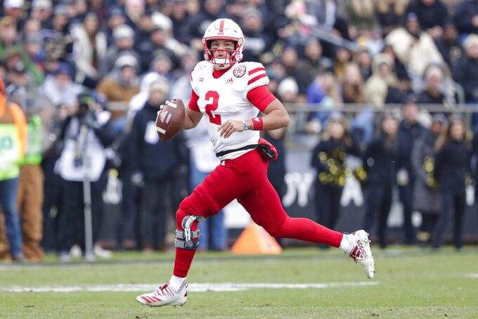 Nebraska quarterback Adrian Martinez (2) looks for a receiver as he scrambles against Purdue during the first half of an NCAA college football game in West Lafayette, Ind., Saturday, Nov. 2, 2019. (AP Photo/Michael Conroy)