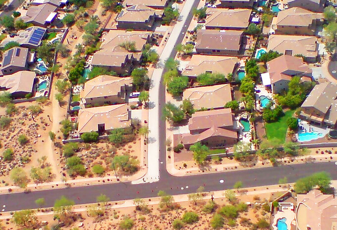 "This Arizona State University photo shows a Phoenix street coated half with a new, lighter-colored pavement at center left while the original blacktop is seen at right on Sept. 10, 2020. A team from Arizona State University is working with the city of Phoenix on a pilot program studying the use of ""cool pavement"" to reduce the heat island effect, a phenomenon that raises temperatures in urban areas covered by asphalt and concrete. (Arizona State University via AP)"