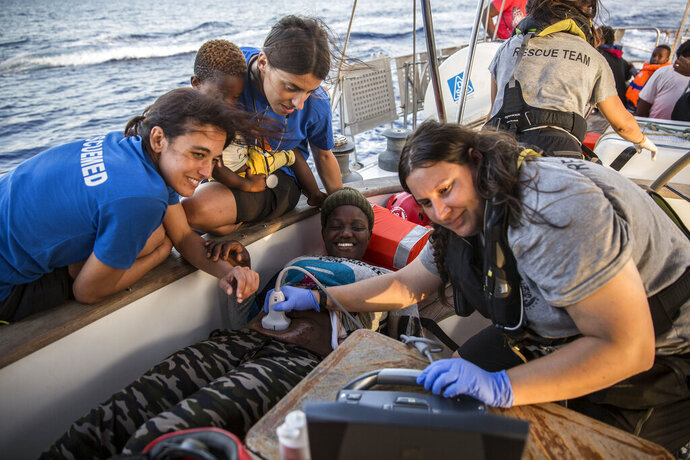 Doctors tend to a pregnant woman on a Mediterranea Saving Humans NGO boat, as they sail off Italy's southernmost island of Lampedusa, just outside Italian territorial waters, on Thursday, July 4, 2019. An Italian humanitarian group whose boat has been barred from docking in Lampedusa said the health of the 54 migrants it rescued at sea is rapidly deteriorating, prompting fears of another standoff with Italy's populist government. Mediterranea Saving Humans said Friday in a tweet that its sailing boat ALEX was off Italy's southernmost island of Lampedusa, just outside Italian territorial waters, and that it has been banned from entering Italian jurisdiction by ministerial decree. (AP Photo/Olmo Calvo)
