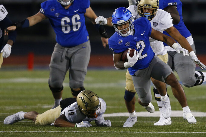 Buffalo running back Ron Cook Jr. gets past Akron safety MyJaden Horton (19) during the second half of an NCAA college football game in Amherst, N.Y., Saturday, Dec. 12, 2020. (AP Photo/Jeffrey T. Barnes)