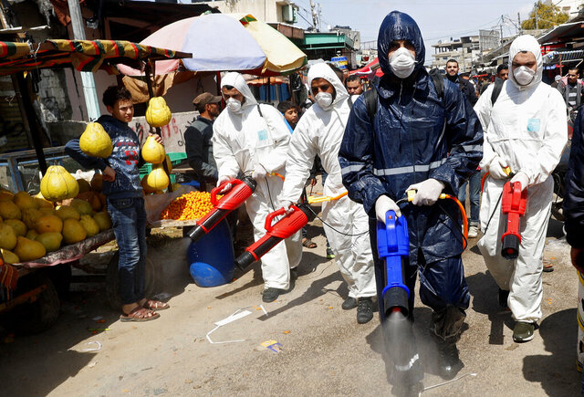 FILE - In this Thursday, March 19, 2020 file photo, workers wearing protective gear spray disinfectant as a precaution against the coronavirus, at the main market in Gaza City. The Gaza Strip has been largely cut off from the rest of the world for more than a decade by an Israeli-Egyptian blockade. But the coronavirus has found a way in. Fearing a widespread outbreak after nine confirmed cases, Gaza's Hamas leaders are racing to build two massive quarantine complexes and prepare the overcrowded territory not equipped to deal with a new health crisis. (AP Photo/Adel Hana, File)