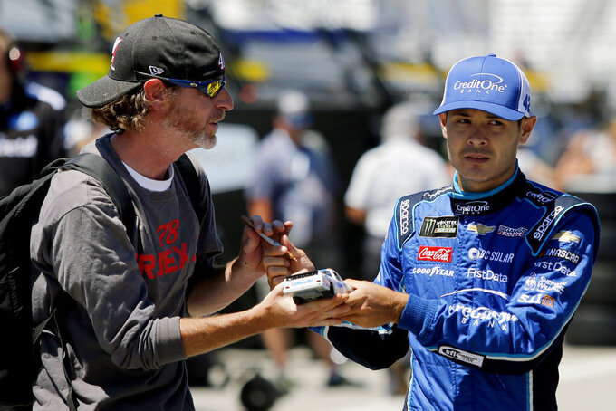 FILE - In this July 20, 2018, file photo, NASCAR Cup Series driver Kyle Larson signs an autograph for a fan wearing a Martin Truex Jr. shirt before auto racing practice at New Hampshire Motor Speedway in Loudon, N.H. Kyle Larson was fired Tuesday, April 14, 2020, by Chip Ganassi Racing, a day after nearly every one of his sponsors dropped the star driver for using a racial slur during a live stream of a virtual race. Larson, in his seventh Cup season with Ganassi and considered the top free agent in NASCAR mere weeks ago, is now stunningly out of a job in what could ultimately be an eight-figure blunder by the star. (AP Photo/Mary Schwalm, File)