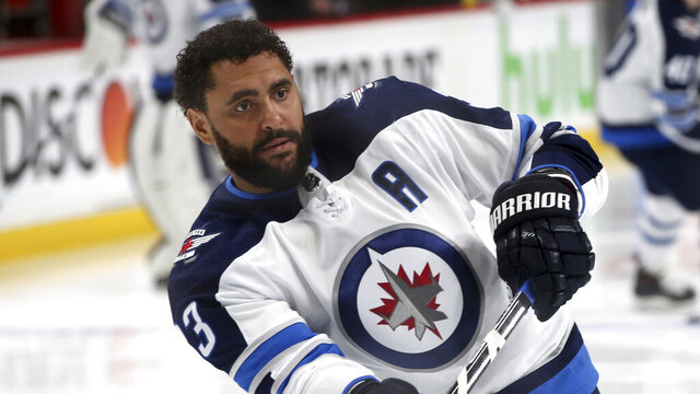 FLE - In this April 17, 2018, file photo, Winnipeg Jets' Dustin Byfuglien warms up before Game 4 of an NHL hockey first-round playoff series against the Minnesota Wild in St. Paul, Minn. The Winnipeg Jets and Dustin Byfuglien have agreed to mutually terminate his contract after a lengthy dispute. (AP Photo/Jim Mone, File)