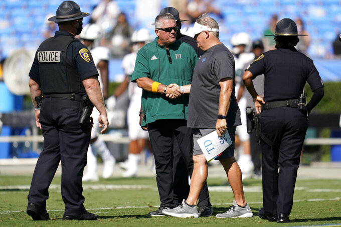 Hawaii head coach Todd Graham, center left, shakes hands with UCLA head coach Chip Kelly after an NCAA college football game Saturday, Aug. 28, 2021, in Pasadena, Calif. UCLA won 44-10. (AP Photo/Ashley Landis)