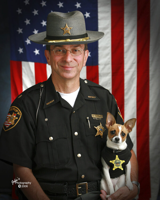 This 2006 image provided by John Hoffart shows then Sheriff Dan McClelland and his small police dog Midge at the Geauga County, Ohio, sheriff's department. Both died on Wednesday, April 14, 2021. McClelland after a lengthy battle with cancer and Midge, perhaps, of a broken heart. The family said they will be buried together. McClelland retired in 2016, after 13 years as sheriff, and 44 total in the department. The last ten with Midge, a drug-sniffing Chihuahua-rat terrier mix certified by Guinness World Records as the smallest police dog on the globe. (John Hoffart via AP)