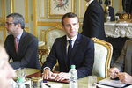 French President Emmanuel Macron flanked by Elysee general secretary Alexis Kohler, left, holds a meeting at the Elysee presidential Palace, in Paris, Monday, March 18, 2019. Macron summoned top security officials Monday after police failed to contain resurgent rioting during yellow vest protests that transformed a luxurious Paris avenue into a battle scene. (Ludovic Marin/Pool Photo via AP)
