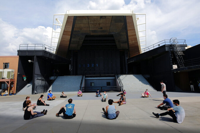 """Stagehands stretch and do pushups behind the Santa Fe Opera ahead of its first shows of the pandemic on Friday, June 18, 2021, outside Santa Fe, N.M. The first performance over the weekend included an unmasked cast and a masked audience. State restrictions on performances and crowds lifted last month, but the opera house is still playing it safe. The performance of """"The Marriage of Figaro"""" was sold out, with some seats empty for distancing. (AP Photo/Cedar Attanasio)"""