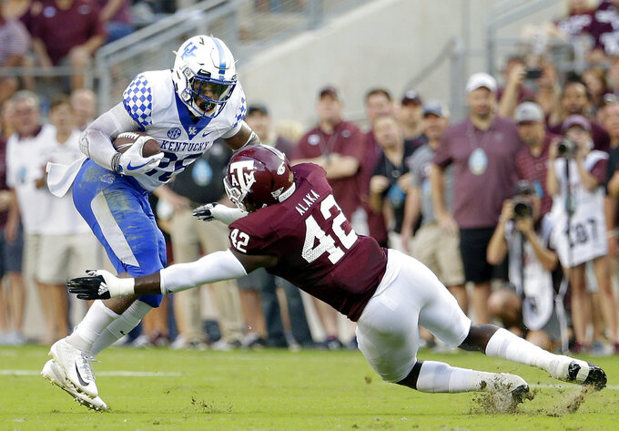 Kentucky running back Benny Snell Jr. (26) is tackled on his run by Texas A&M linebacker Otaro Alaka (42) during the first half of an NCAA college football game Saturday, Oct. 6, 2018, in College Station, Texas. (AP Photo/Michael Wyke)