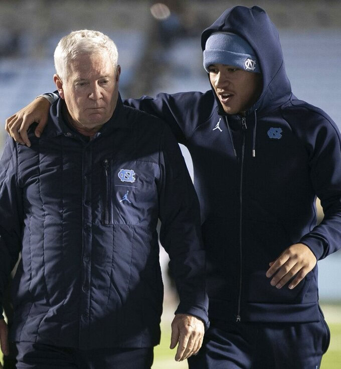 North Carolina coach Mack Brown is consoled by Cam'Ron Kelly as they leave the field following a 38-31 loss to Virginia during an NCAA college football game Saturday, Nov. 2, 2019, in Chapel Hill, N.C. (Robert Willett/The News & Observer via AP)
