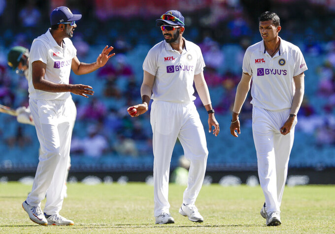 Indian bowlers Ravichandran Ashwin, left, Jasprit Bumrah and Navdeep Saini, right, talk during play on day three of the third cricket test between India and Australia at the Sydney Cricket Ground, Sydney, Australia, Saturday, Jan. 9, 2021. (AP Photo/Rick Rycroft)