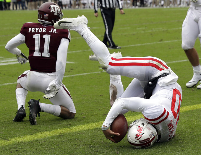 Mississippi Rebels quarterback Jordan Ta'amu (10) tumbles into the end zone after rushing for a touchdown as Texas A&M defensive back Larry Pryor (11) defends during the first half of an NCAA college football game Saturday, Nov. 10, 2018, in College Station, Texas. (AP Photo/David J. Phillip)