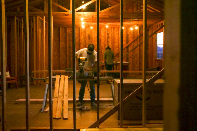FILE - In this Nov. 4, 2019, file photo, Bobbie Chandler, and his wife, Jenna, work in the home they are building in Santa Rosa, Calif. Chandler's parents' home of 20 years and thousands of other structures were destroyed by the Tubbs Fire and other wine country wildfires of 2017. California state and local officials are incentivizing rebuilding in areas destroyed by wildfires at a time when people should be redirected away from those areas if the state wants to reduce the economic and human impact of increasingly destructive wildfires, according to a report published Thursday, June 10, 2021. (AP Photo/Lacy Atkins, File)
