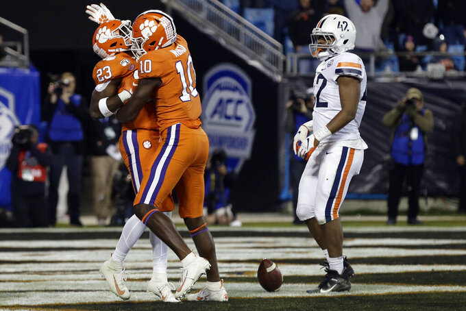 Clemson wide receiver Joe Ngata (10) and Clemson running back Lyn-J Dixon (23) celebrate a touchdown during the second half of the Atlantic Coast Conference championship NCAA college football game as Virginia linebacker Nick Jackson (42) looks on in Charlotte, N.C., Saturday, Dec. 7, 2019. Clemson won 62-17. (AP Photo/Gerry Broome)