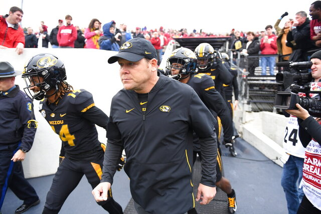 In this Friday, Nov. 29, 2019 photo, Missouri head coach Barry Odom leads his team onto the field to play Arkansas during an NCAA college football game in Little Rock, Ark. Missouri fired Odom on Saturday, Nov. 30, 2019,  ending the four-year stay of a respected former player who took over a program in disarray but could never get the Tigers over the hump in the brutal SEC. (AP Photo/Michael Woods)