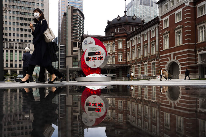 FILE - In this March 23, 2020, file photo, countdown clock for the Tokyo 2020 Olympics is reflected in a puddle of water outside Tokyo Station in Tokyo. IOC officials say the Tokyo Olympics will open on July 23 and almost nothing now can stop the games from going forward. (AP Photo/Jae C. Hong, File)