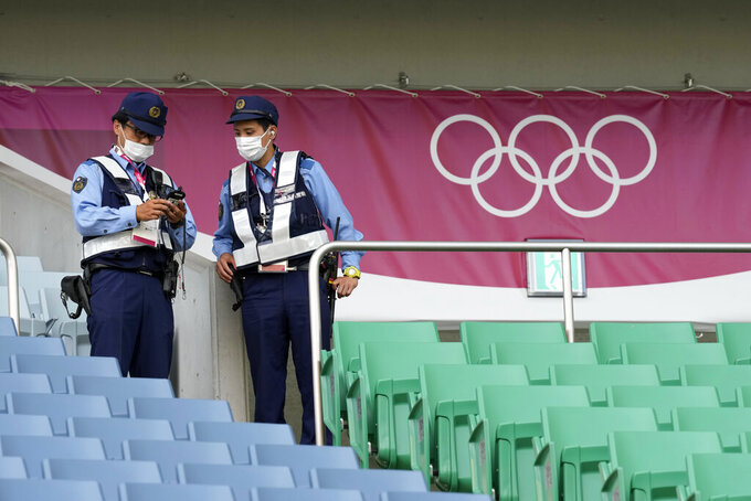 Police officers check the stands before a women's soccer match between Sweden and Australia at the 2020 Summer Olympics, Saturday, July 24, 2021, in Saitama, Japan. (AP Photo/Martin Mejia)