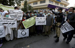 Members of Pakistan Hindu Council hold a protest against the attack on a Hindu temple in the northwestern town of Karak, in Karachi, Pakistan, Thursday, Dec. 31, 2020. Pakistani police arrested 14 people in overnight raids after a Hindu temple was set on fire and demolished by a mob led by supporters of a radical Islamist party, officials said. The temple's destruction Wednesday in the northwestern town of Karak drew condemnation from human rights activists and the minority Hindu community. (AP Photo/Fareed Khan)