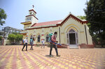 Indian volunteers spray disinfectants at a church in Jammu, India, Sunday, June 7, 2020. India whose coronavirus caseload is fifth highest in the world is Monday reopening places of worship after a period of more than two months lockdown. (AP Photo/Channi Anand)