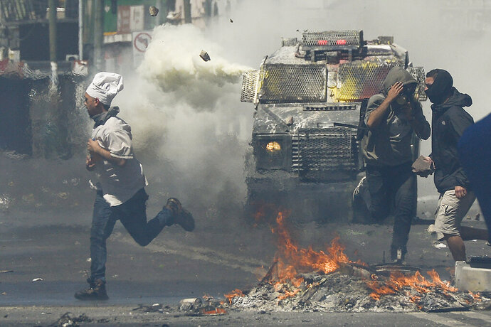A man wearing a chef's hat runs for cover as anti-government protesters clash with police in Valparaiso, Chile, Thursday, Oct. 24, 2019. President Sebastian Pinera made more economic concessions Thursday announcing a freeze on a 9.2% rise in electricity prices until the end of next year, to try to curb a week of deadly protests over price increases and other grievances. (AP Photo/Matias Delacroix)