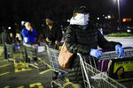 FILE- In this March 20, 2020, file photo, customers wearing protective masks and gloves wait in line at a Stop & Shop supermarket in Teaneck, N.J. New Jersey Gov. Phil Murphy said on Thursday, Oct. 22, 2020 that New Jersey's climbing number of COVID-19 cases are beginning to spread to northern counties around New York. (AP Photo/John Minchillo, File)