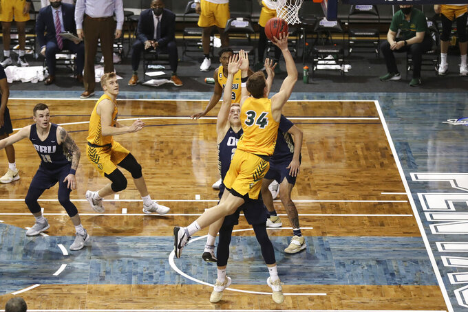 North Dakota State forward Rocky Kreuser (34) shoots over an Oral Roberts defender during an NCAA college basketball game for the  Summit League men's tournament championship Tuesday, March 9, 2021, in Sioux Falls, S.D. (AP Photo/Josh Jurgens)