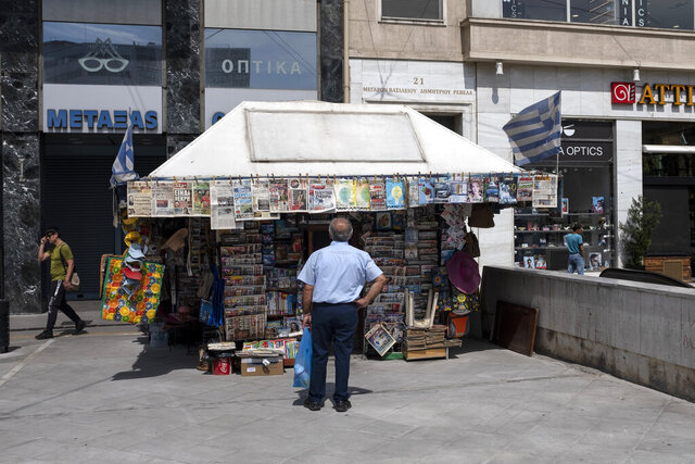 A man checks newspapers' front pages at a kiosk in Athens, on Friday, June 5, 2020. The European Commission says Greece is likely to suffer deepest recession in the eurozone this year, but first quarter growth figures were better than expected. (AP Photo/Yorgos Karahalis)
