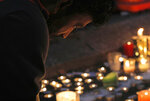 A mourner lights a candle during a vigil to commemorate victims of Friday's shooting, outside the Al Noor mosque in Christchurch, New Zealand, Monday, March 18, 2019. Three days after Friday's attack, New Zealand's deadliest shooting in modern history, relatives were anxiously waiting for word on when they can bury their loved ones. (AP Photo/Vincent Yu)