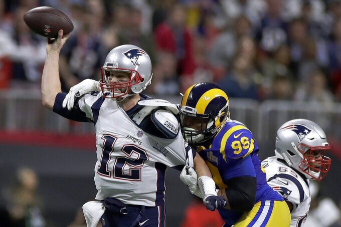"File-This Feb. 3, 2019 file photo shows New England Patriots' Tom Brady (12) passing under pressure form Los Angeles Rams' Aaron Donald (99) during the first half of the NFL Super Bowl 53 football game in Atlanta. Brady will soon slip on his sixth Super Bowl ring, and Herb Adderley is the only other man on the planet who can relate to that level of success as the National Football League celebrates its 100th season. ""It's going to be a long time, another 100 years, before somebody wins himself six titles,"" said Adderley, the Hall of Fame cornerback for Vince Lombardi's great Green Bay Packers teams of the 1960s. (AP Photo/Carolyn Kaster, File)"
