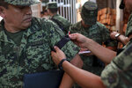 A Mexican army officer is given a black ribbon on his sleeve during the wake for Alfredo Gonzalez Munoz, a soldier that died during a massive gun battle in the city of Culiacan between drug cartel gunmen and members of the army and the police, in Veracruz, Mexico, Saturday, Oct. 19, 2019. The gunfight in the city of roughly 800,000 residents was triggered Thursday by an attempt to arrest Ovidio Guzman, son of convicted drug lord Joaquin