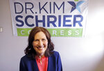 FILE - In this March 30, 2018, file photo, Dr. Kim Schrier, a candidate in Washington state's 8th District race, poses for a photo in Issaquah, Wash. Schrier, a Democratic, is running against Republican Dino Rossi in an open and true toss-up race for the seat to succeed retiring incumbent, Rep. Dave Reichert. The district includes the eastern suburbs of Seattle and stretches into the rural Cascade Mountain region. (AP Photo/Elaine Thompson, File)